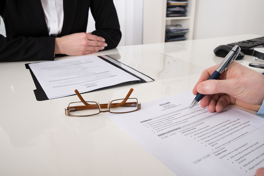 Close-up Of Businessperson With Resume And Pen In Office