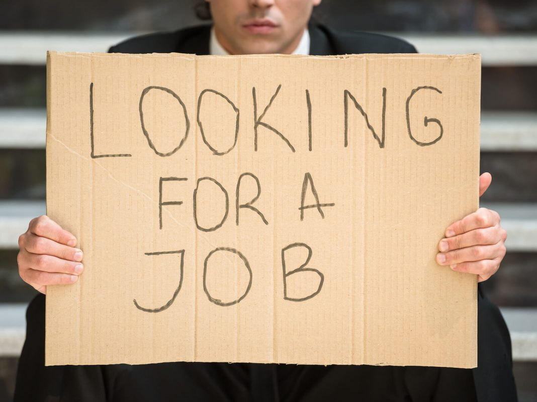 unemployed man holding a sign: Looking for a job