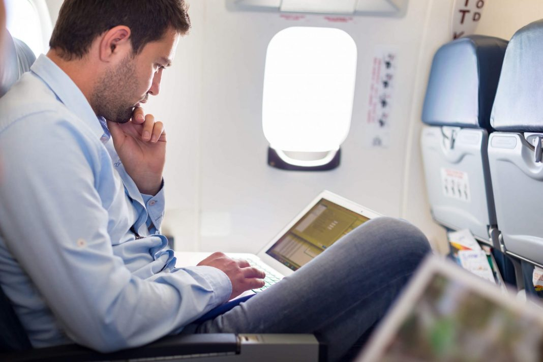 Man working on laptop in a plane